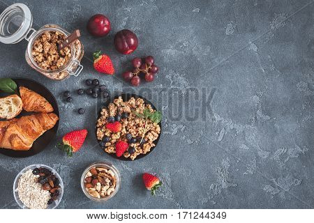Healthy breakfast with muesli fruits berries nuts on grunge background. Flat lay top view