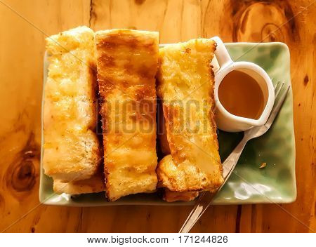Toast bread served with sweet syrup ,toast butter served with sweetened condensed milk on wooden table. Pour the milk toast breakfast with sun light. background.