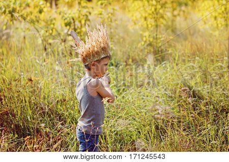 Little boy have a crown from dry grass on the head and swords in hands.