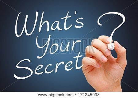 Hand writing What Is Your Secret with white marker over dark background.