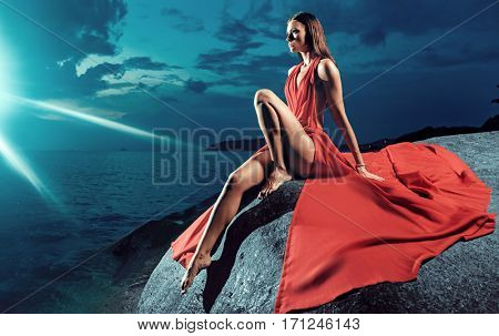 Glamorous brunette in the moon rays at the sea