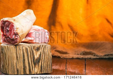 Butcher's block with raw shank and loin. Fire light background
