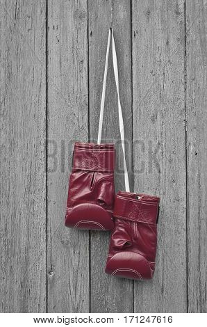 Red boxing leather gloves hangs on a nail gray cracked wooden wall