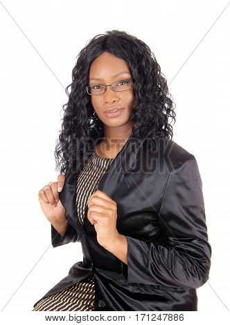 An young African American businesswoman sitting in a black jacket and curly hair wearing classes isolated for white background.
