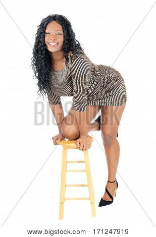 A beautiful young African American woman in a short dress kneeling with one leg on a chair isolated for white background.
