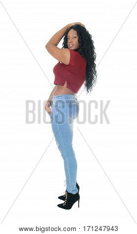 A beautiful African American woman standing in jeans in profile for white background with one hand on head.