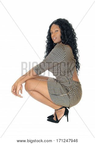 A beautiful African American woman in a short dress and long curly black hair crouching isolated for white background.