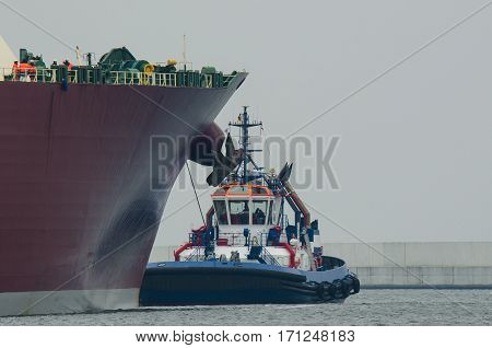 TUG AT GAS CARRIERS - Tug insures large tanker in the harbor