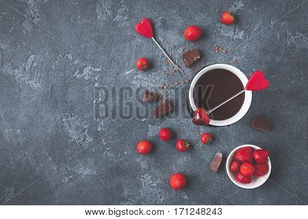 Chocolate fondue with fresh strawberry on dark background. Valentine's Day. Flat lay top view