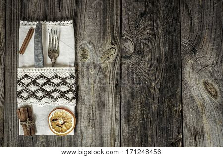 Metal utensils decorated with a napkin on a gray wooden surface with cracks and scuffed the empty space on the right