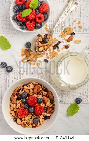 Homemade granola with fresh berries on white wooden background, top view