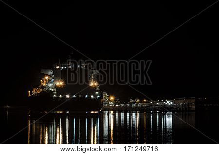 NIGHT IN PORT MARINE - LNG terminal at night and moored gas tanker