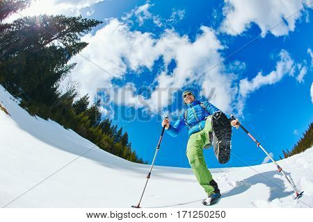 hiker with backpack on the trail in the Carpathians mountains at winter. picture of hiker taken on wide angle from low point