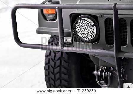 Detail with military vehicle headlight and protection crash bars