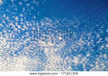 Small white cumulus clouds against the blue sky background.