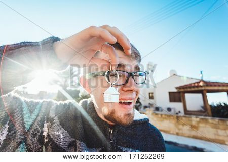 Happy funny man holds house keys on house shaped keychain in front of a new home.