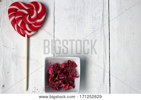 Candy on a stick in the form of the heart, the petals of dried flowers and nail polish: beauty, grooming, greeting card Happy Valentine's Day (14 February), International Women's Day (8 March), the day the mother and other holidays