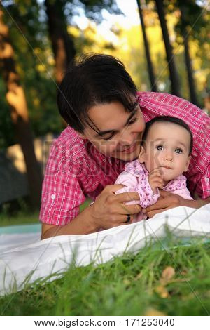 Happy young father lying with his cute happy toddler girl on the grass