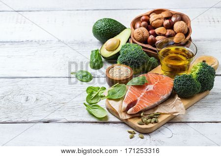 Selection of healthy fat sources food, salmon fish avocado olive oil pumpkin seeds nuts broccoli green spinach on a white rustic wooden table. Copy space background