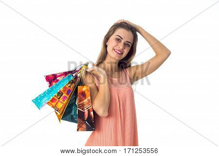 beautiful girl keeps the ball behind his head and suddenly hand holds colored packets with gifts is isolated on a white