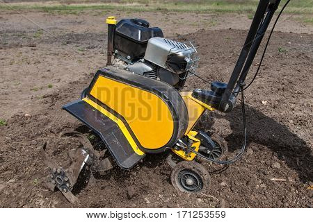 Garden tiller to work tractor cultivating field at spring loosens soil by petrol cultivator close-up
