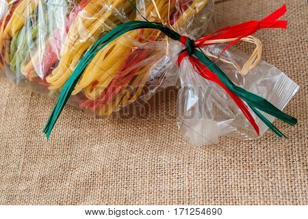 Package with a dry Italian pasta tied ribbons in the color of the flag. Traditional Italian pasta, concept image with colors of Italian flag