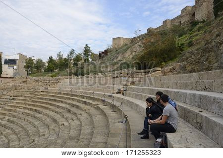 MALAGA, SPAIN - DECEMBER 8, 2015: People at the seats of the Roman theater at the foot of the Alcazaba fortress in Malaga Spain.