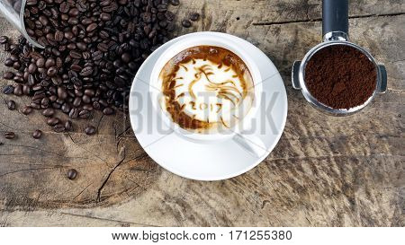 2017 rooster coffee. Cappuccino coffee and sweet chocolate brownies cake. A cup of latte, cappuccino or espresso coffee with milk put on a wood table with dark roasting coffee beans. Drawing the foam milk on top.