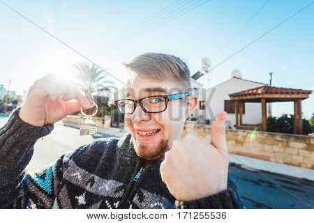 Portrait of a young man holding out new house key while gesturing thumbs up