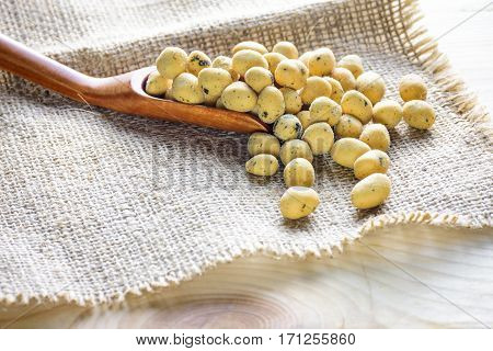Coated peanuts seaweed flavor with wood spoon on hemp sack wooden table