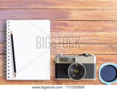 Top view of wooden table with office supplies. Office desk table with notebookpencil and vintage camera. copy space for design