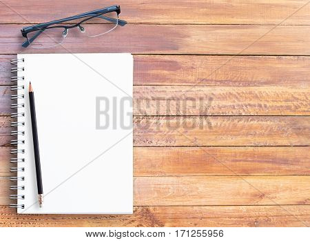 Top view of wooden table with office supplies. Office desk table with notebookpencil and glasses. copy space for design