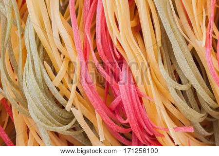 Italian pasta, three color from durum wheat with vegetables on the kitchen textiles, background. Top view. Macro. for use as background image or as texture