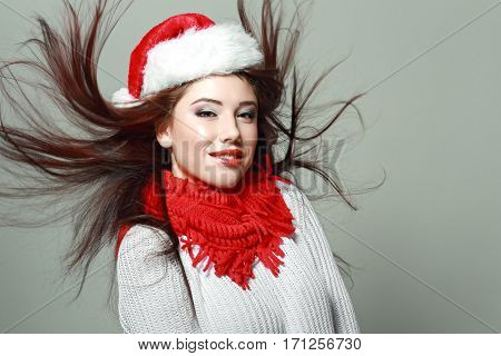 portrait of young beautiful woman with flying hair on neutral background in photostudio