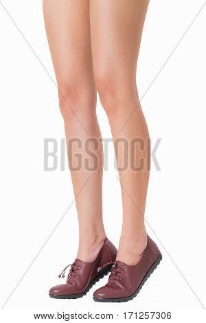 Woman beautiful long legs and healthy skin in standing legs pose wearing vintage fashion leather shoes Isolated on white background.