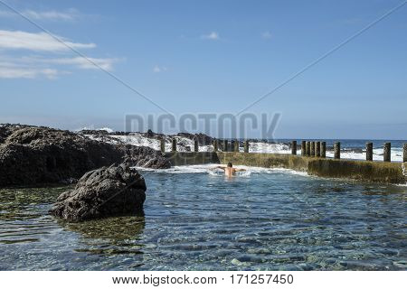 A man enjoys a refreshing swim in the still clear blue waters of a natural rock pool on the Tenerife coast near Alcala while waves from the Atlantic Ocean crash over the volcanic rocks and sea wall