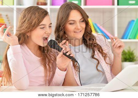 Happy teenage grl and her mother singing karaoke at home