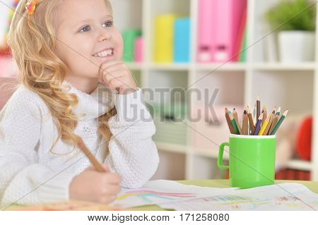 cute little girl drawing in her room
