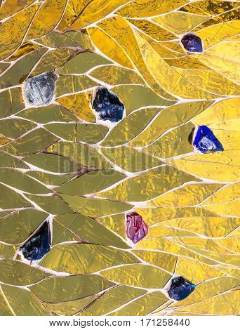 golden mosaic decorated with colored stones background. Shiny yellow gold color decorative texture Bright brilliant glossy metallic textured empty backdrop