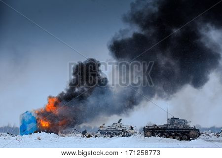 Winter view of the german tanks (panzers) with burning house in the battle. Reconstruction of the winter defensive battles of the Red Army in WWII (1944 year).
