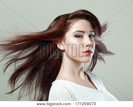 portrait of young beautiful woman with flying hair posing in photostudio