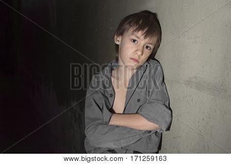 Sad lonely little boy in a dark cellar