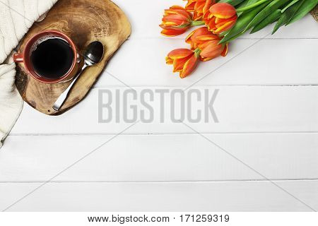 Overhead shot of a morning cup of black coffee with a bouquet of orange and yellow tulip flowers and a cozy knit throw blanket over white wood table top. Flat lay top view style.