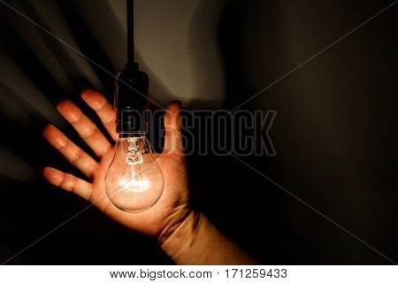 light bulb and hand with dark background