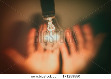 abstract light bulb and hand with dark background