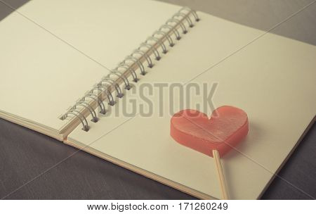 Heart stick on blank notebook diary on black table