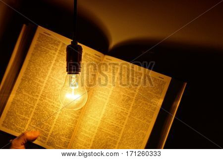 electric bulb illuminating a book close up
