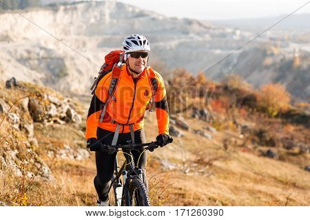low angle view of cyclist standing with mountain bike on trail at sunset. Cycler in the helmet and sunglasses with red backpack. Beautiful landscape with hill and horizon. Travel in the countryside.