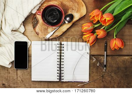 Overhead shot a bouquet of an open book cell phone coffee and flowers over a wood table top ready to plan an agenda. Flat lay top view style.