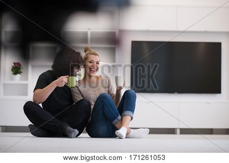 portrait of young happy beautiful couple sitting on the floor and drinking coffee in their new home